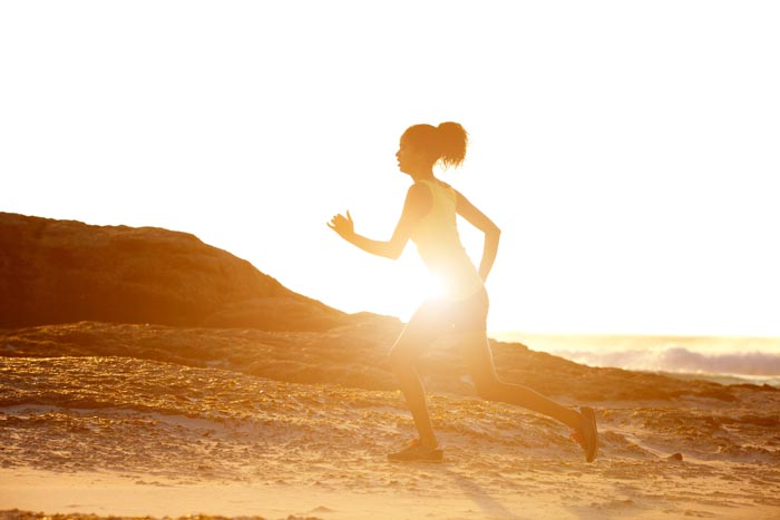Full length side portrait of a female runner with sunset